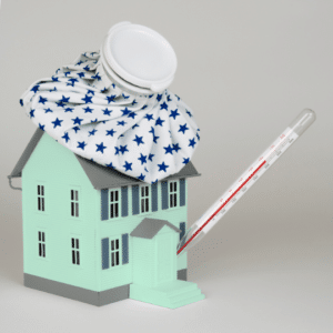 green toy house with thermometer in the front door and cooling pack on the roof showing quarantine and lockdown