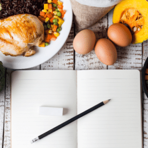 Open journal with pencil and eraser surrounded by healthy food