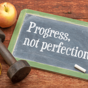 """Image of blackboard with dumbells and apple. Written on the blackboard is """"progress, not perfection"""""""