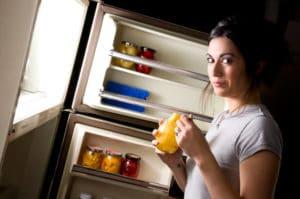 women snacking with fridge door open at night - it is dark
