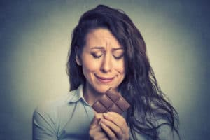 woman looking upset and eating chocolate - pcos cravings