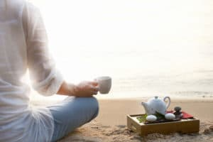 Woman meditating and drinking tea on beach