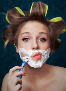 woman shaving her face with curlers in her hair. PCOS hormonal acne is linked to high androgens that also cause facial hair in women