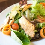 grilled-salmon-ceasar-salad-on-white-plate