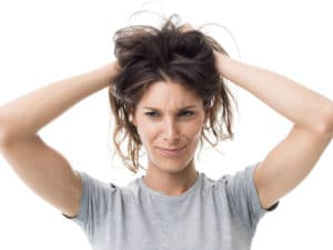 Women with bith hands in greasy hair in grey t shirt